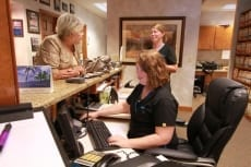Image: Front office staff talks with patient | Patient Resources - Lail Family Dentistry, Duluth GA